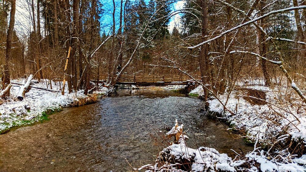 Die alte Holzbrücke, die die Wanderer über den Fluss führt