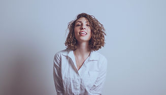 With unkempt hair and a slightly wrinkled white blouse Molly smirks at the camera