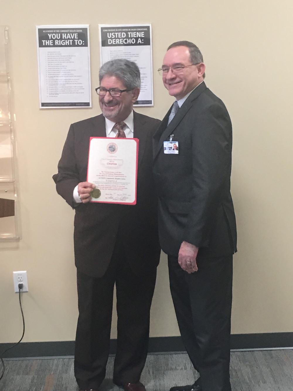 Fitchburg Mayor Stephen DiNatale (left) presents CHC President & CEO John DeMailia (right) with an official citation