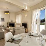 Stue og kjøkken i første etasje. Lyse og delikate farger. Sofa-gruppe, satelitt-TV og peis i stua, og kjøkken med spisebord i motsatt hjørne.  Ny AC i stue/kjøkken sommeren 2021.