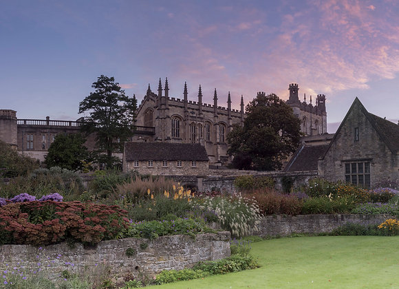 Dawn over Oxfords Christchurch cathedral, with flower borders and lawn.