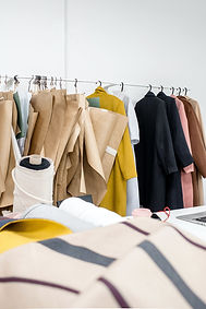 A rack of clothing coats, and technica flat pattern designs hanging on the rack
