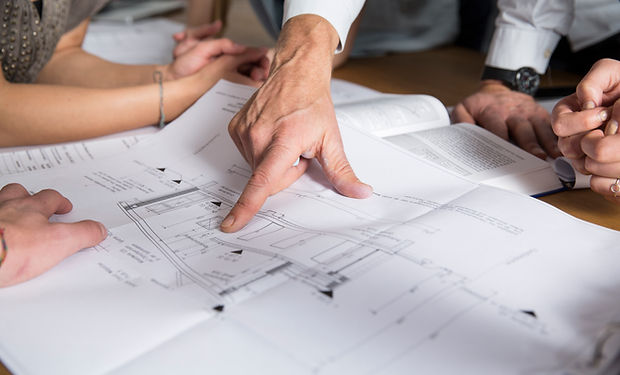 Man looking and pointing at architectural plans.