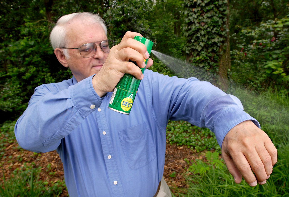 Man spraying himself with DEET