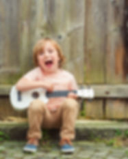 Little happy boy plays his guitar or uku