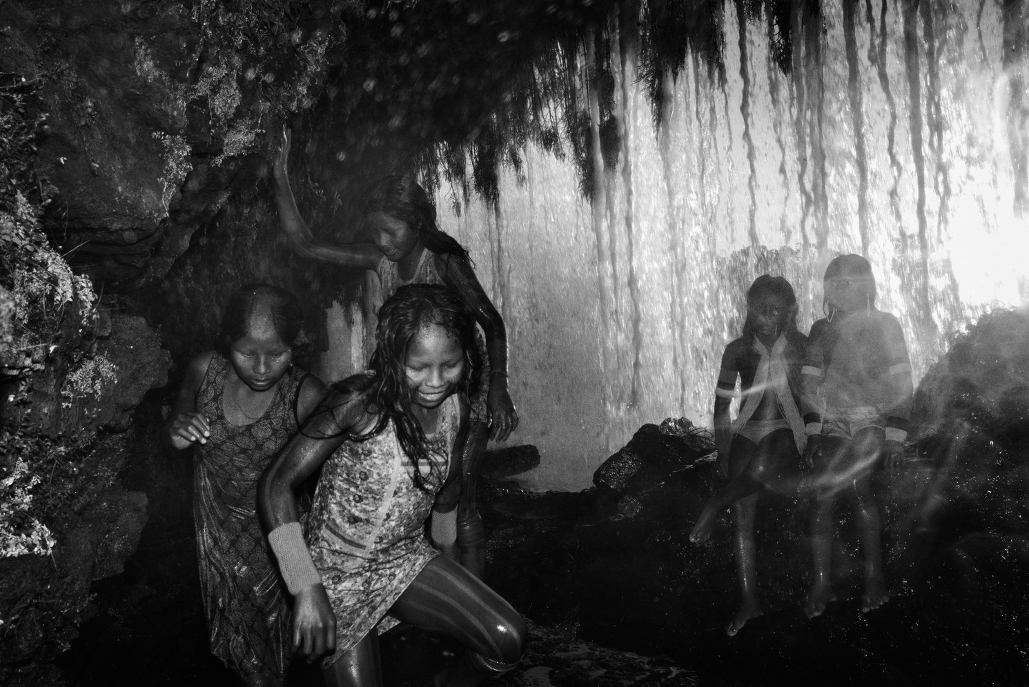 Kayapo children play behind a waterfall in the Kubenkrãnken indigenous village, in southern Pará state. The Kayapo have only been in contact with non-indigenous society since the 1960s. Their land serves as a crucial barrier to deforestation advancing from the south.