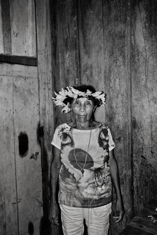 """Katisiká Karipuna portrayed inside her house in the Panorama village. She is one of the four tribespeople who still speaks the Karipuna language. The majority of the tribe was wiped out by diseases following contact with Amazon settlers in the 1970's, during Brazil's military governments' drive to occupy the Amazon. Today the Karipuna population number 40 memebers. The Karipuna Indigenous territory in Brazil's North-western state of Rondonia sits on the so called """"arc of deforestation,"""" the agricultural frontier advancing into the Amazon forest and one of the front lines of the country's deadly conflict over land and resources. Since 2015, the land has been increasingly targeted by loggers and land grabbers but the tribesmen so far say their complaints have fallen on deaf ears. In Rondonia, death threats are serious. The state consistently tops the list of land conflict killings, with 15 already in 2017, according to watchdog group Comissão Pastoral da Terra."""