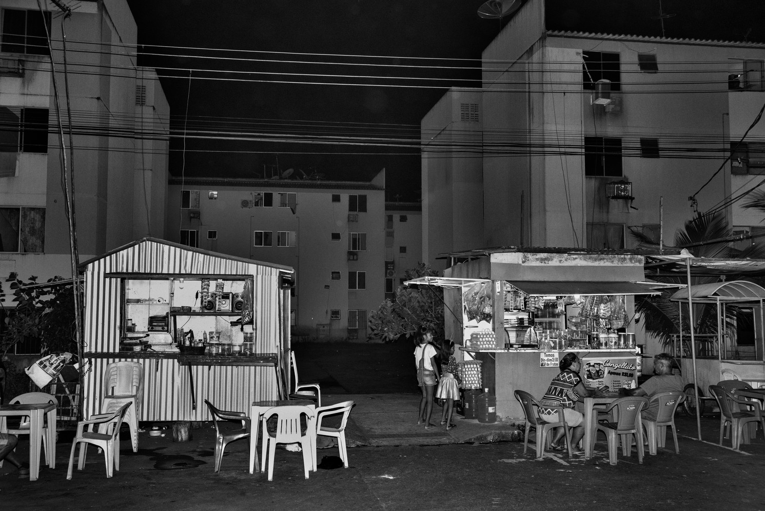 Residents enjoy evening snacks at kiosks at the Viver Melhor – Live Better - public housing complex in Manaus. Built with federal government funds and inaugurated in 2014 it's the largest public housing complex in Brazil. More than 55 thousand people live here. It's located on the far northern outskirts of the city, more than an hour's drive from downtown. Manaus' most powerful drug gang A Família do Norte – The Northern Family – controls security here as well all illegal activity.