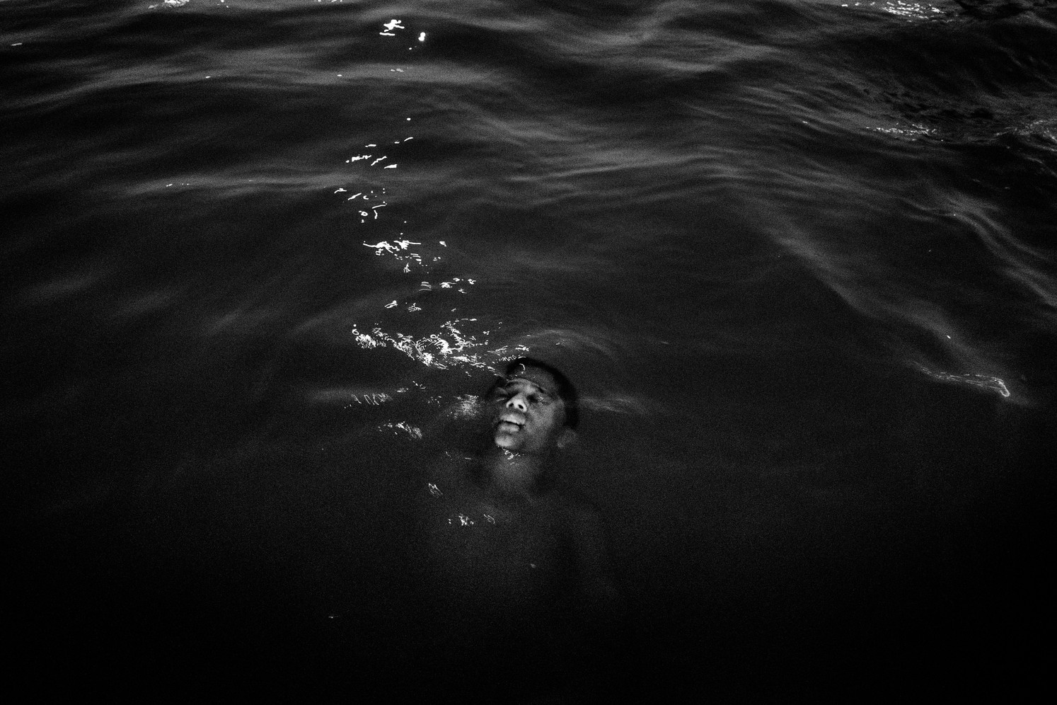 A boy taking a bath at night in the Tocantins river, a tributary of the Amazon River in the state of Pará.