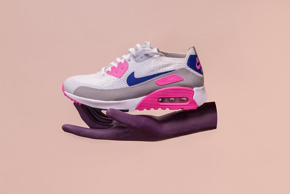 Purple hand holding a Nike sneaker