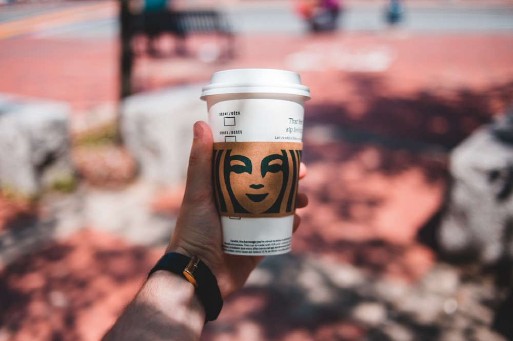 a person holding a Starbucks coffee cup