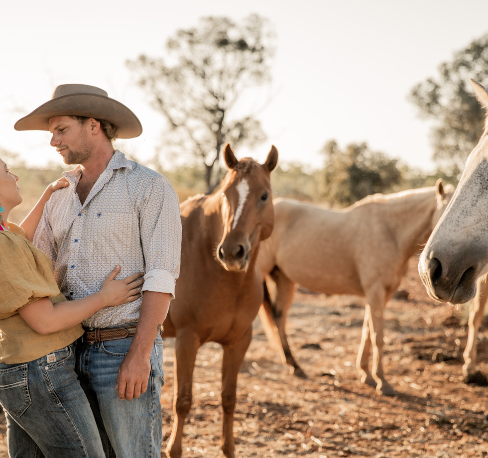 Couple in love surrounded by their horses