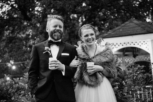 new couple laughs at their wedding inblack and white