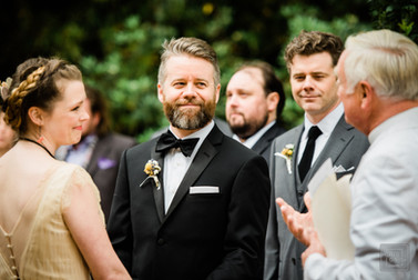 groom looks at his father who is also the officiant durring the ceremony