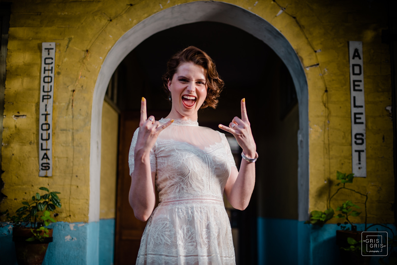 metal bride poses with hand horns durring bridal portrait shoot with new orleans themed backdrop