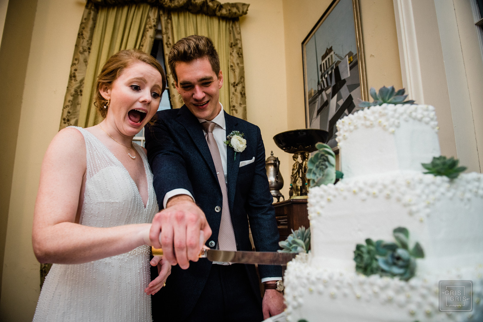 bride shows emotion when cutting cake durring their reception at the benachi house