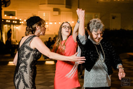 women dance with their grandmother durring wedding reception