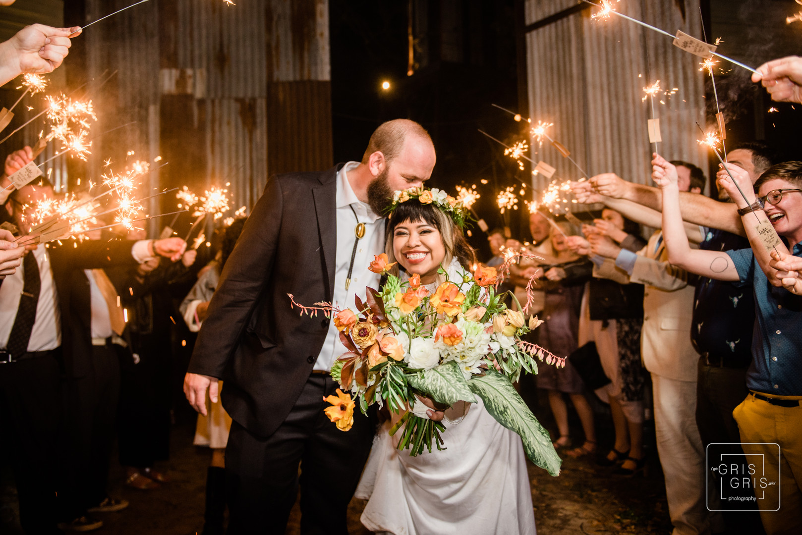 bride and groom exit with sparkler at the new orleans music box