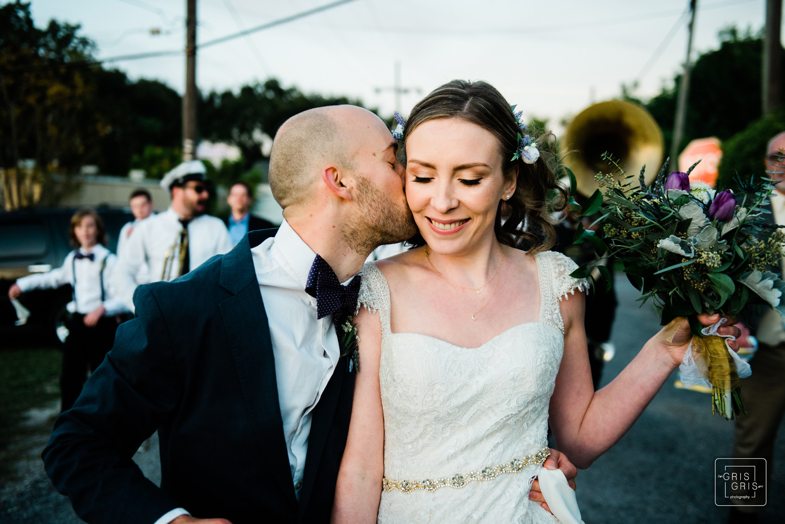 Groom kisses his bride durring parade in new orleans