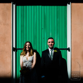 bride and groom pose for photo in front of new orleans french quarter building