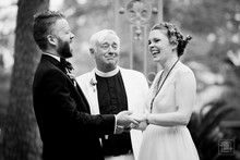 black and white image of bride and groom laughing durring their wedding