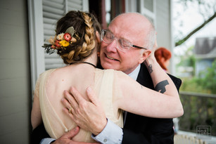 father hugs bride after first look on front porch of benachi house