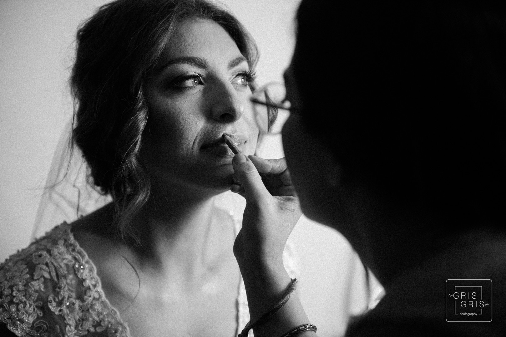 bride get finishing touche of makeup before her wedding
