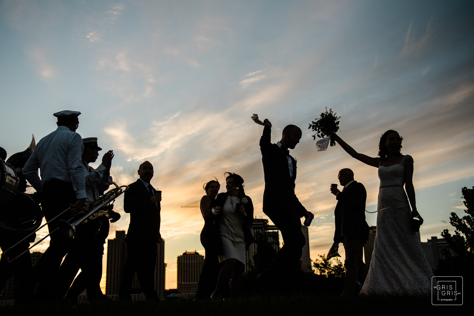 Bride and groom parade with jazz band on the new orleans levee