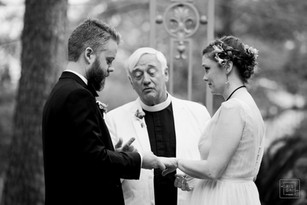 groom puts ring on bride hand as the father who is also the officant watches