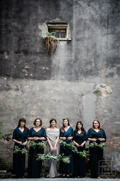 bridal party portrait with gray french quarter like wall as backdrop