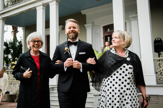 son walks mothers down aisle in front yard wedding at the New Orleans Benachi house