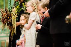 flower girl looks at photographer durring outside wedding