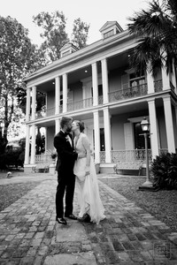 married couple kisses in front of the new orleans benachi house