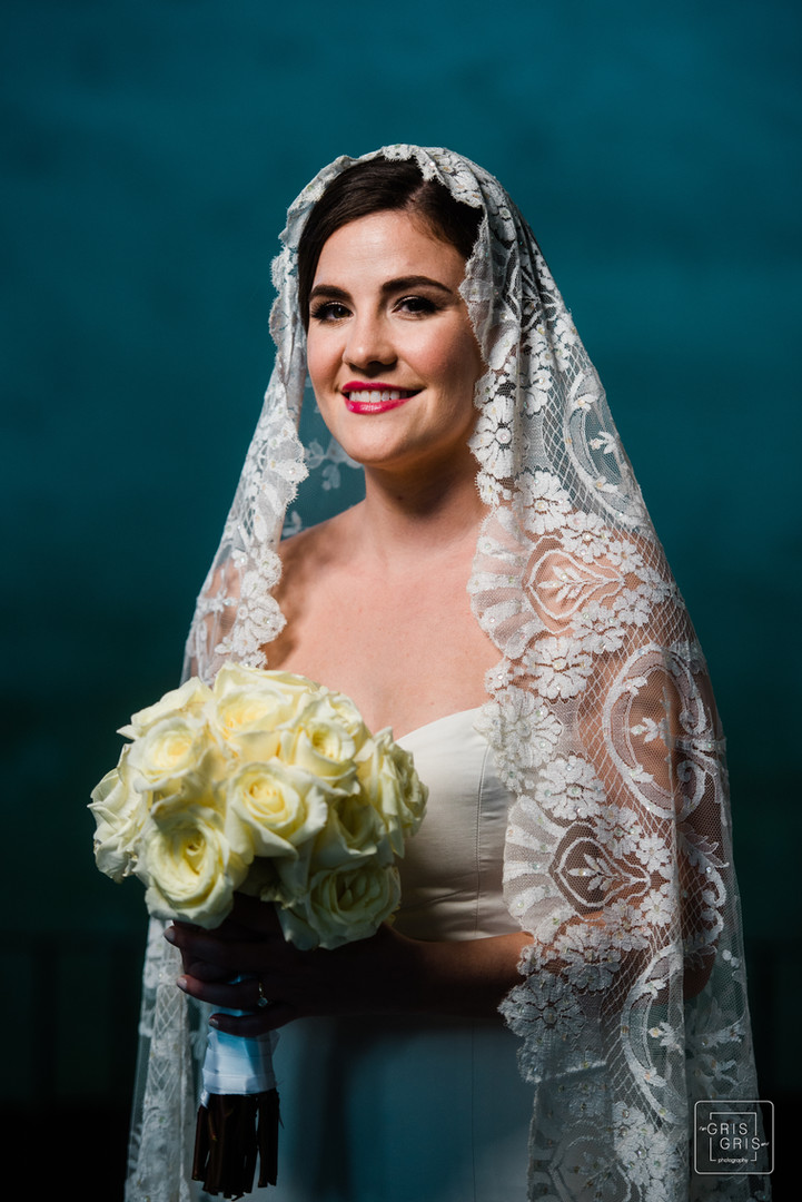 Bride poses for portrait on front porch of house in New Orleans