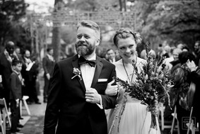wedding couple smile after they  walk down aisle smilling
