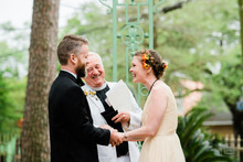 bride groom and officiant laugh in front yard wedding