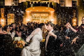 bride impromptuly kisses her husband while exiting from lakefront airport terminal