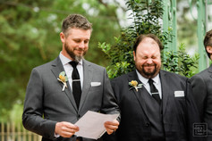 best man reads candid speach while groomsmen laugh