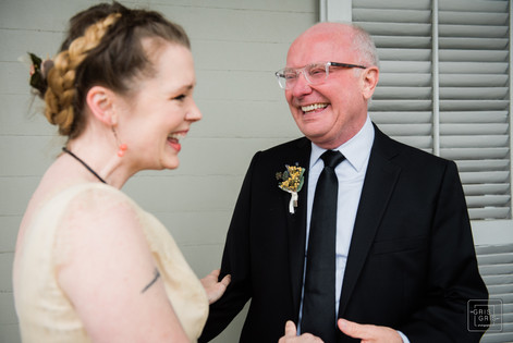 father and daughter laugh after first look on wedding day