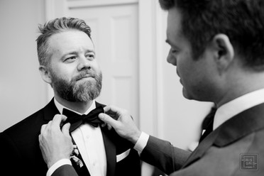 grooms brother fixes his tie in new orleans wedding