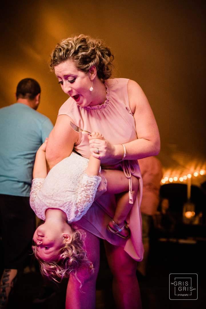 candid shot of mother dancing with her daughter durring reception