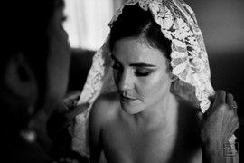 mother of bride helping her daughter put on her viel before her wedding