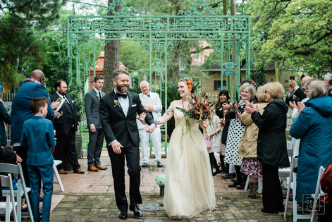bride and groom walk down the aisle after they just got married
