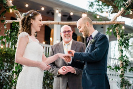 groom put ring on brides hand durring wedding ceremony at compass point events