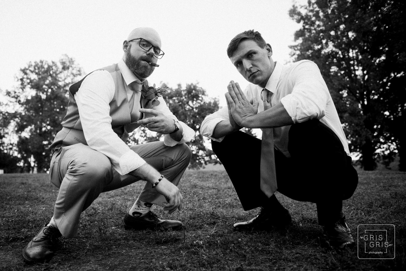 two groomsmen strike gangster pose on durring their best freinds wedding