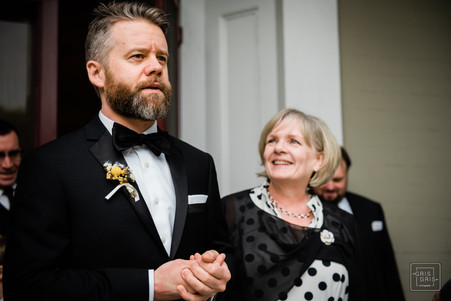 mother of groom looks at her son as he leads her down aisle for wedding