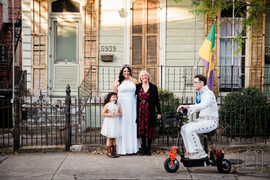 a family portrait of 3 genereations of woman in front of new orleans uptown house while elvis on a scooter heads to mardi gras parade