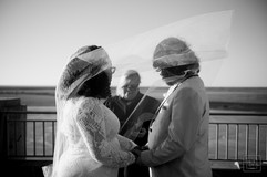 bride and groom look at the wedding officiant durring ceremony at the new orleans lakefront airport