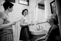 a bride and bridemaids do makeup in bathroom and laugh before wedding