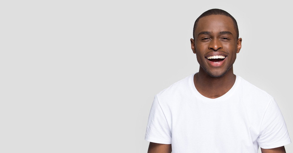 African guy in t-shirt look at camera laughing having ultra white toothy smile pose aside isolate on grey wall copy space for your advertise_edited.jpg